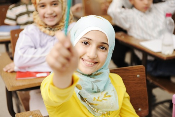 Adorable Muslim girl in classroom with her friends